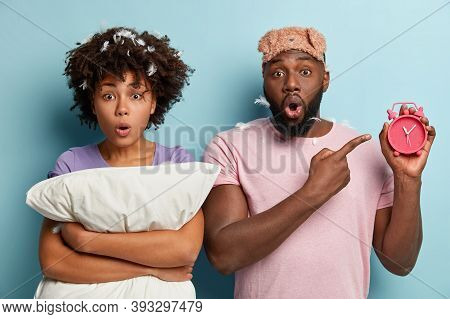 Indoor Shot Of Surprised Dark Skinned Guy Shows Late Time On Alarm Clock, Says Wife They Overslept,