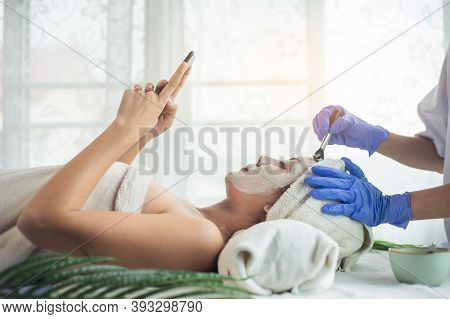 Asian Woman Relax Use Smartphone And Getting Facial Face Care By Beautician At Spa Salon, Closeup Fa