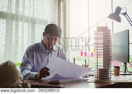 Asian Man Architect Working At Home, Professional Architect Looking Blueprint For Project Making Mod