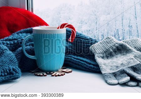 Winter Christmas background. Cup with Christmas candy cane, woolen scarf and gloves on windowsill and winter scene outdoors. Winter Christmas background with concept of spending Christmas winter time at cozy home