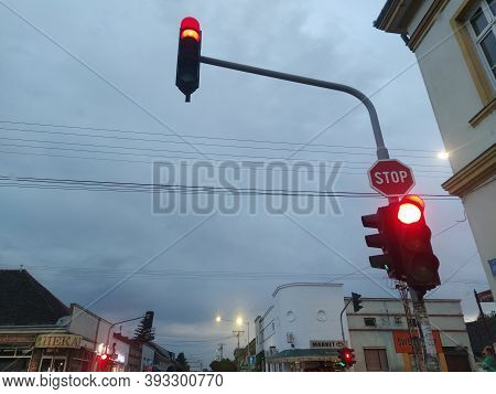 Street With Traffic Lights And Road Signs. Cars Stop In Front Of The Intersection. Shooting From A C