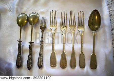 Antique Forks And Spoons In Different Sizes At The Flea Market.