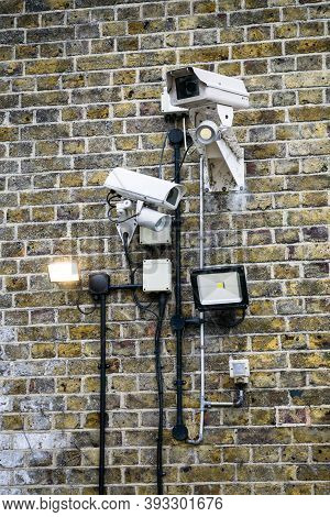 A Group Of Cctv Cameras And Floodlights On A Brick Wall.