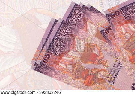 500 Sri Lankan Rupees Bills Lies In Stack On Background Of Big Semi-transparent Banknote. Abstract P