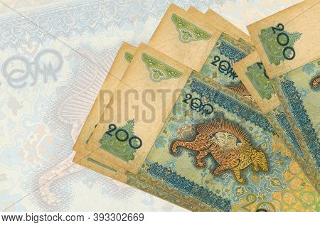 200 Uzbekistani Som Bills Lies In Stack On Background Of Big Semi-transparent Banknote. Abstract Pre