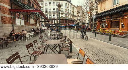 Brussels, Belgium: Street Cafe With Steel Furniture And Cyclists Driving Around An Old City With Res
