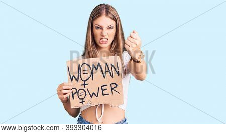 Young beautiful blonde woman holding woman power banner annoyed and frustrated shouting with anger, yelling crazy with anger and hand raised