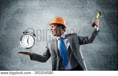 Businessman Going To Crash With Hammer Alarm Clock. Young Contractor In Business Suit And Safety Hel