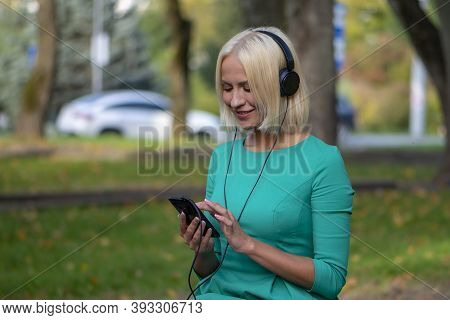 A Young Woman 25-30 Years Old In The Park Listening To Music With Headphones From Her Phone 3.