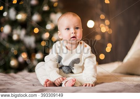 Little Cute Baby Boy In Winter Body Posing In The Studio Against Christmas Background. Copy Space.
