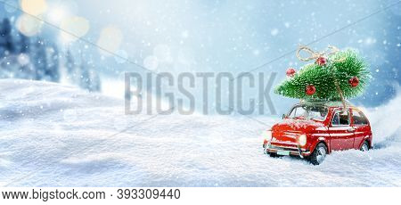Retro Toy Car Carrying Christmas Tree On Roof In Snowy Winter Forest. Christmas Background. Holidays