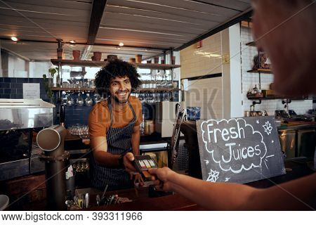 Portrait Of Smiling Waiter Holding Credit Card Swipe Machine While Customer Typing Code In Modern Ca