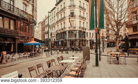 Brussels, Belgium: Narrow Streets Of City With Old Cafe Stores, Some Visitors And Empty Tables Outsi