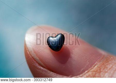 Macro shot of the heart shaped rock lying on the fingernail
