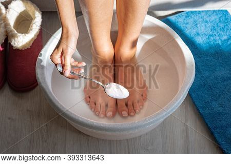 Woman Put Spoon Of Baking Soda In Bath With Hot Water For His Feet. Homemade Bath Soak For Dry Feet