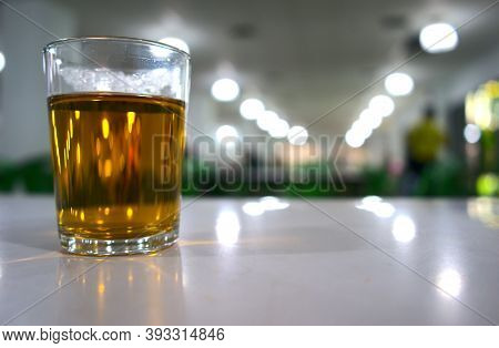 Hot Tea Drink With Bokeh Background. A Cylinder Glass Of Golden Clear Water Beverage On Table At Can