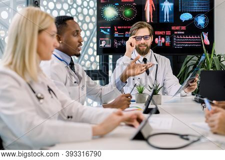 Medical Team, Caucasian And African Men, Blond Caucasian Lady, Sitting At The Table In Meeting And C