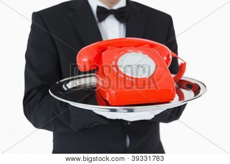 Waiter holding red dial phone on silver tray
