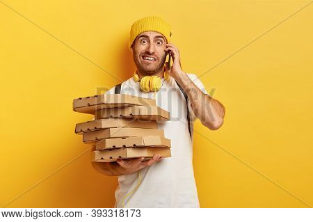Photo Of Pizza Man Receives Orders From Customers Via Smart Phone, Holds Many Carton Boxes With Fast