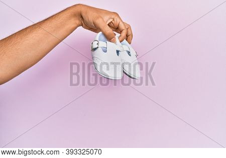 Hispanic hand holding baby shoes over isolated pink background.