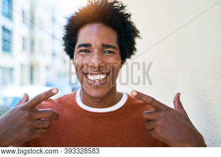 Young handsome african american man wearing casual clothes smiling happy. Standing with big smile on face pointing mouth with fingers walking at town street.
