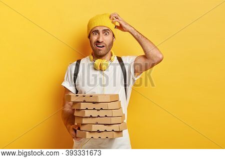 Photo Of Puzzled Doubtful Delivery Man Scratches Head, Holds Takeaway Pizza Boxes, Delivers Fast Foo