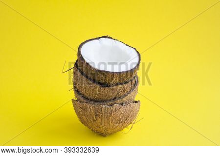 Halves Coconuts On The Yellow Background With Copy Space