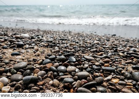 Variety Of Smooth Pebbles, Rocks And Stones At Seashore. Quiet Peaceful Beach With Water Waves Comin