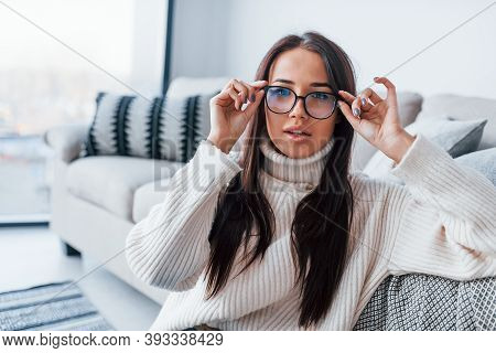 Young Beautiful Woman In Glasses Sitting At Home Alone.