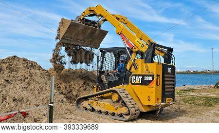 Port Aransas, Tx - 29 Feb 2020: Working Man Drives A Yellow Cat 289d Front Loader Machine To Empty A