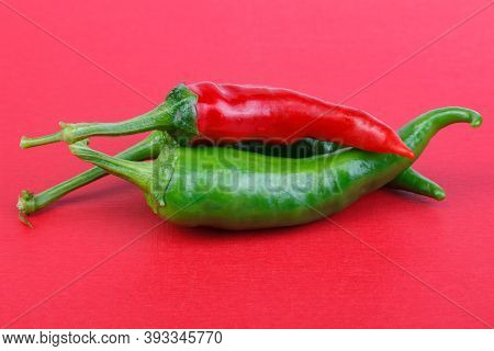 Chili Paprika, On A Red Background. Healthy Food. Fresh Vegetables . Chili Peppers On A Red Backgrou