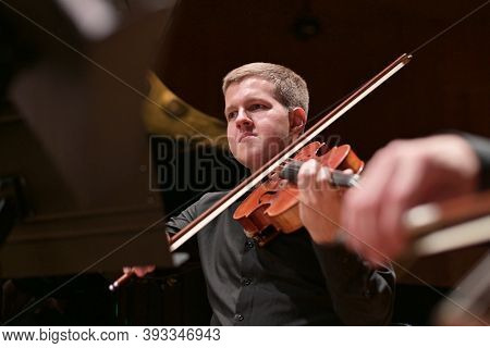 Young Male Violinist Playing The Violin To The Accompaniment Of The Orchestra, Bottom View