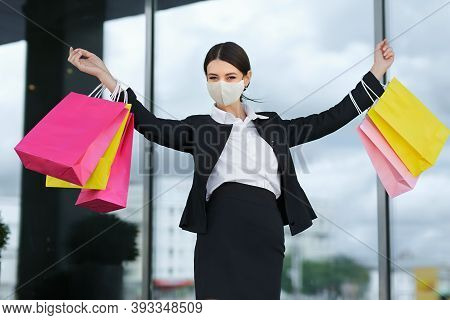 A Girl In A Business Suit With Colorful Bags And A Lots Of Sales Near The Shopping Center, Raised He