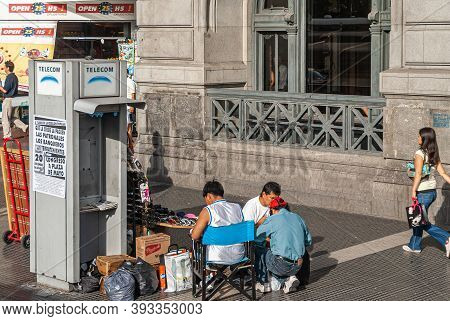 Buenos Aires, Argentiana- December 19, 2008: Ambulant Sunglasses Vendor Sits Near Defunct Telephone