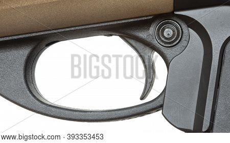 Trigger And Safety On A Shotgun With A Gold Colored Receiver