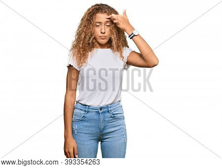 Beautiful caucasian teenager girl wearing casual white tshirt pointing unhappy to pimple on forehead, ugly infection of blackhead. acne and skin problem