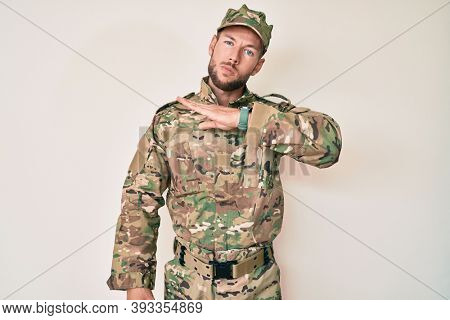 Young caucasian man wearing camouflage army uniform cutting throat with hand as knife, threaten aggression with furious violence