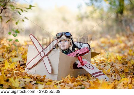A Happy Child Dreams Of Traveling In An Airplane And Plays An Airplane Pilot. The Kid Sits In A Card