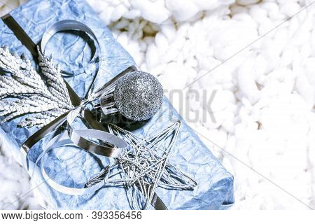 Christmas Presents With Gift Box In Silver Blue Color Decorated With Pine Cones And Twigs On White B