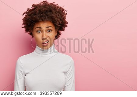 Discontent Woman With Afro Haircut, Smirks Face, Sees Something Unpleasant, Wears Hoop Earrings, Cas