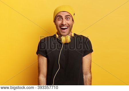Waist Up Shot Of Joyous Optimistic Man Smiles Broadly, Has Happy Reaction On Pleasant Surprise, Spen