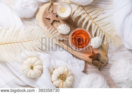 Cosy still life for winter and autumn with glas of pink wine, pumpkin cookie, woll and warm sweater