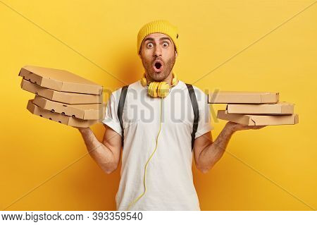 Isolated Shot Of Surprised Delivery Man Holds Several Carton Boxes With Italian Pizza In Both Hands,