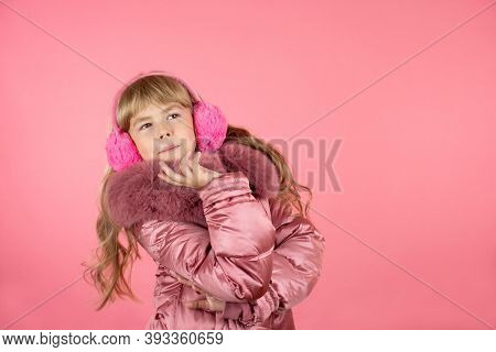Little Girl In A Winter Pink Coat On A Pink Background. Little Fashionista Trying On A Pink Coat. Li