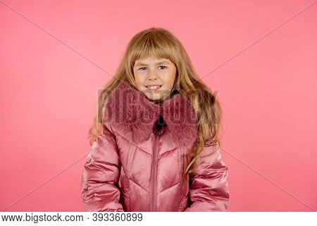 Little Girl In A Winter Pink Coat On A Pink Background. Little Fashionista Trying On A Pink Coat.