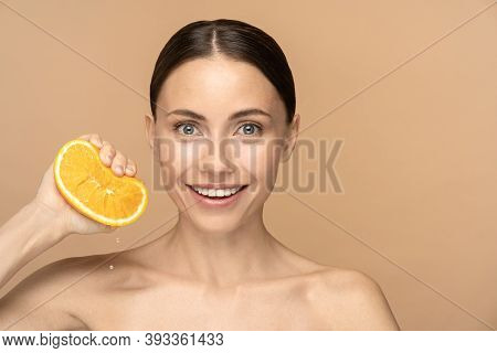Woman With Perfect Face Skin, Combed Hair, Squeezing Orange. Smiling Female With Natural Makeup And