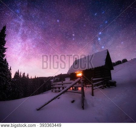 Fantastic night landscape glowing by milky way. Dramatic wintry scene with snowy house. Carpathian mountains, Ukraine, Europe.