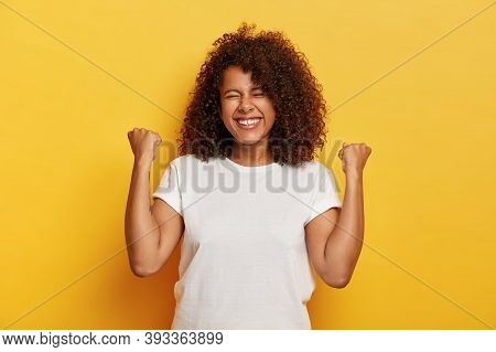 Isolated Shot Of Beautiful Successful Woman With Curly Hair, Raises Clenched Fists, Celebrates Trium