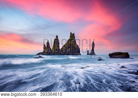Basalt rock formations Troll toes on black beach with pink sunset clouds. Great purple sky glowing on background. Reynisdrangar, Vik, Iceland