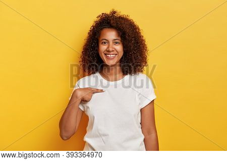 Smiling Cheerful Dark Skinned Girl Points At Herself, Shows Mockup Space On White T Shirt, Happy Bei